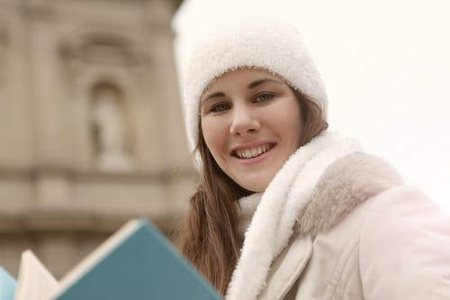 Woman in White Fur Coat Holding a Blue Book