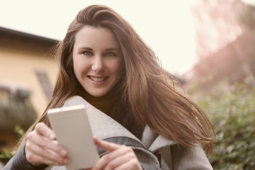 Smiling Woman Holding White Cellphone