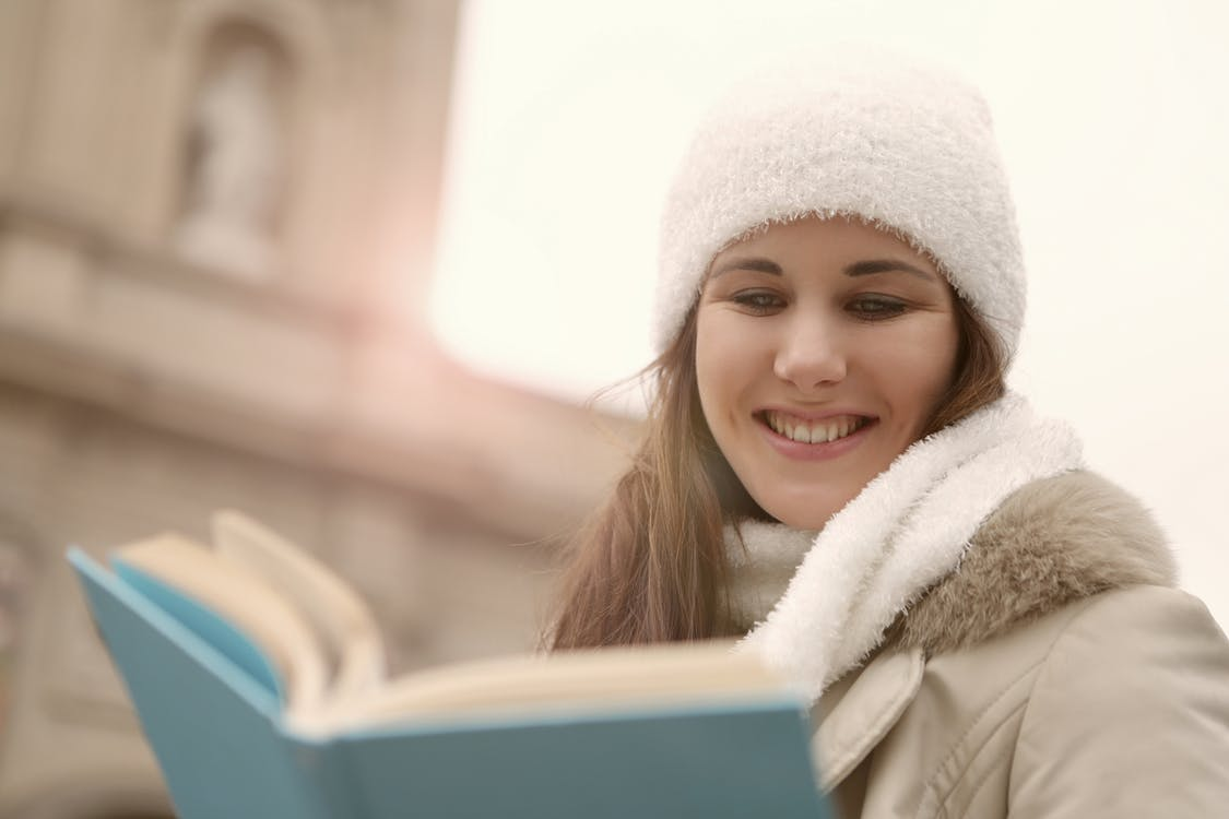 A Happy Woman in White Knitted Beanie Reading a Book