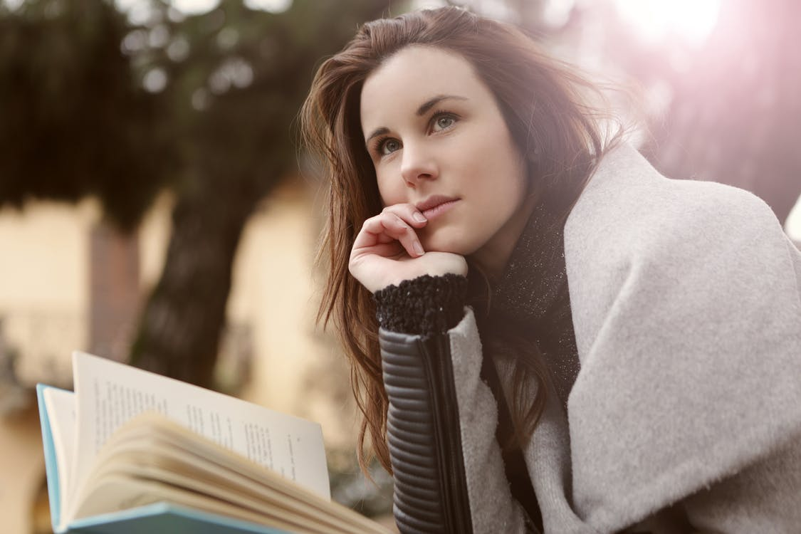 Pensive Woman in Gray Coat Holding Book