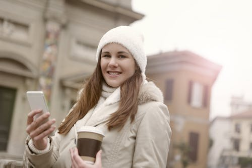 Woman in White Knit Cap Holding Brown Disposable Cup