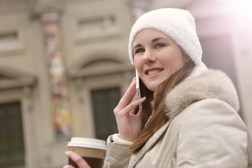 Woman in White Coat Holding White Smartphone