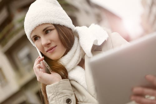 Woman in White Bonnet and White Scarf Using Smartphone