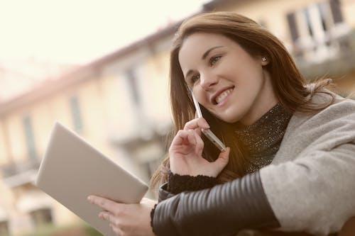 женщина в серой рубашке с длинным рукавом с серебряным Ipad и мобильным телефоном