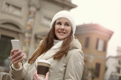 Woman in White Knit Cap Holding Brown and White Disposable Cup