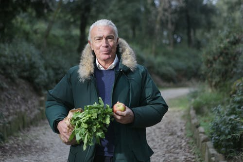 Man in Green Fur Coat Holding Vegetable and Apple Fruit