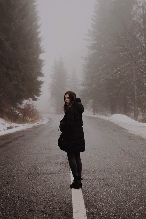 Woman in Black Coat Standing Standing in the Middle of Road