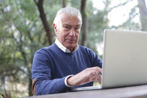 Man in Blue Sweater Typing on Computer Laptop