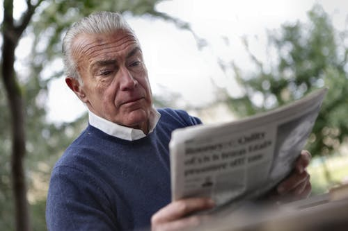 Man in Blue Sweater Reading Newspapers