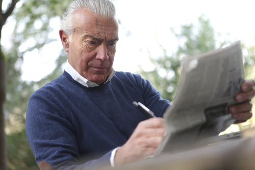 Man in Blue Sweater Holding Pen and Reading Newspaper