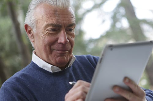 Man in Blue Sweater Holding Silver Ipad