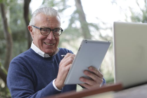 Man in Blue Sweater Holding White Tablet Computer