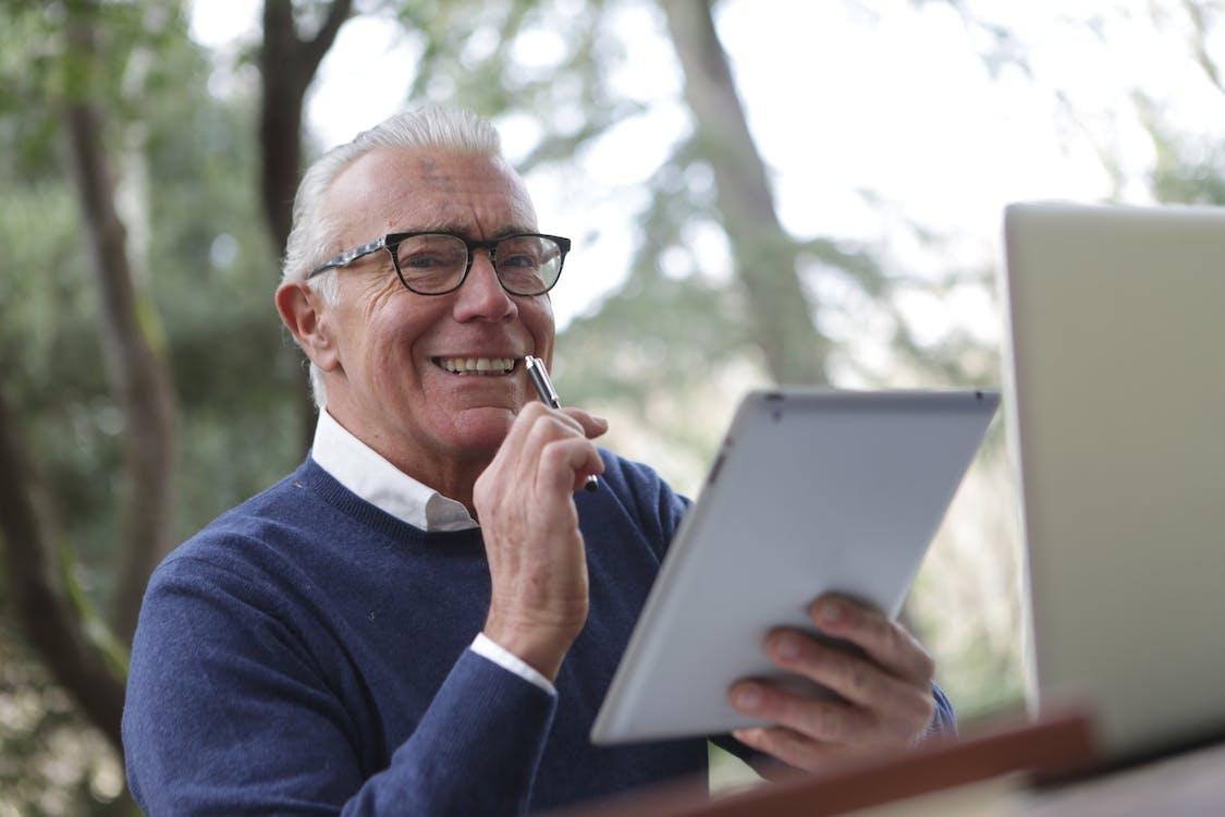 Homem De Suéter Azul Segurando Um Computador Tablet Branco