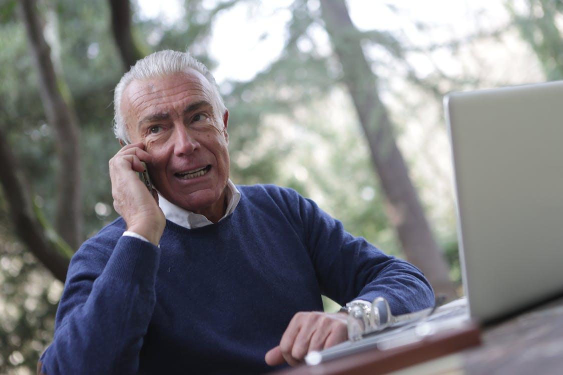 Man in Blue Sweater Sitting Near Wooden Table