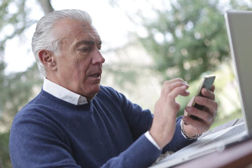Man in Blue Sweater Holding Smartphone