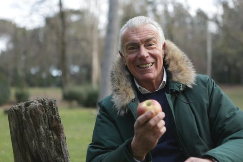 A Joyful Man Holding a Fresh Apple Fruit