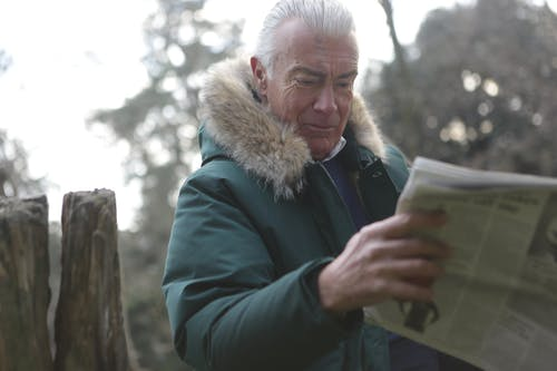 Man in Green Parka Jacket Reading News Paper