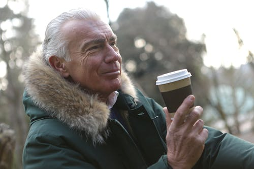 Elderly man Holding a Brown Coffee Cup
