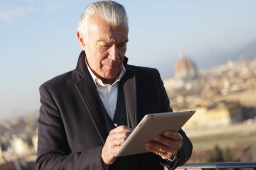 Man in Black Suit Holding Silver Ipad
