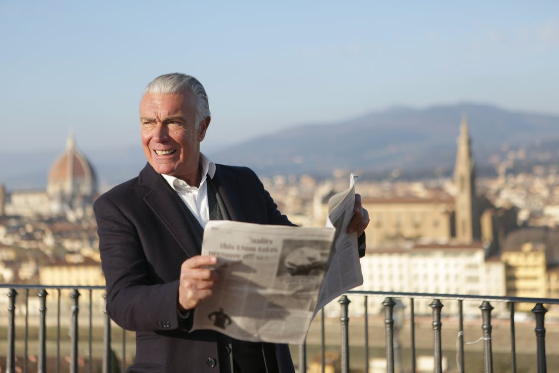 Man in Black Suit Jacket Holding  a Newspaper