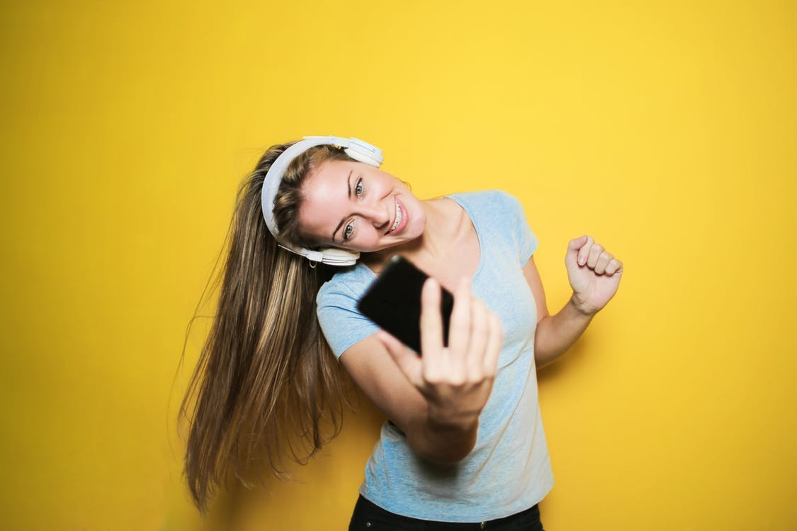 Satisfied woman taking selfie on smartphone in studio