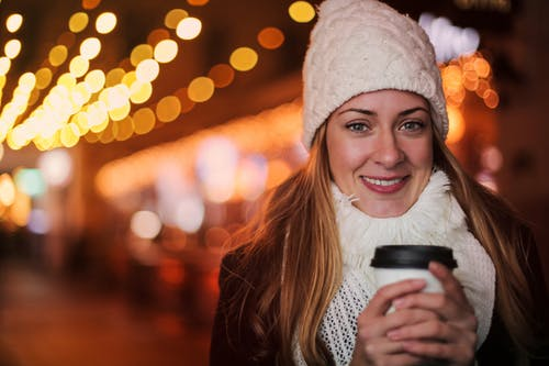 Smiling woman in city warming hands with takeaway coffee