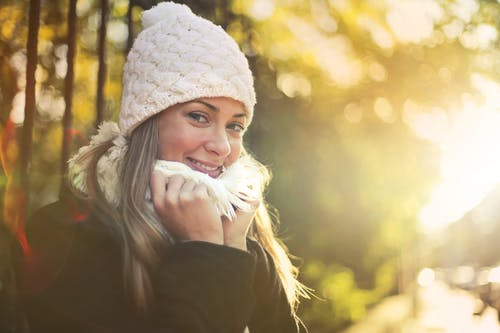 Young content female wearing warm hat and scarf standing in city garden and enjoying weekend while smiling and looking at camera