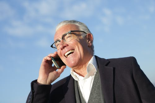 Cheerful senior businessman talking on smartphone on street