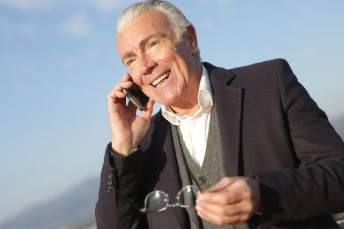 Mature businessman having conversation on smartphone in city