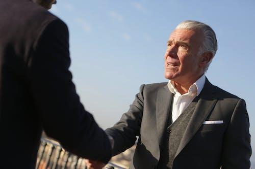 Elderly businessman shaking hands with partner