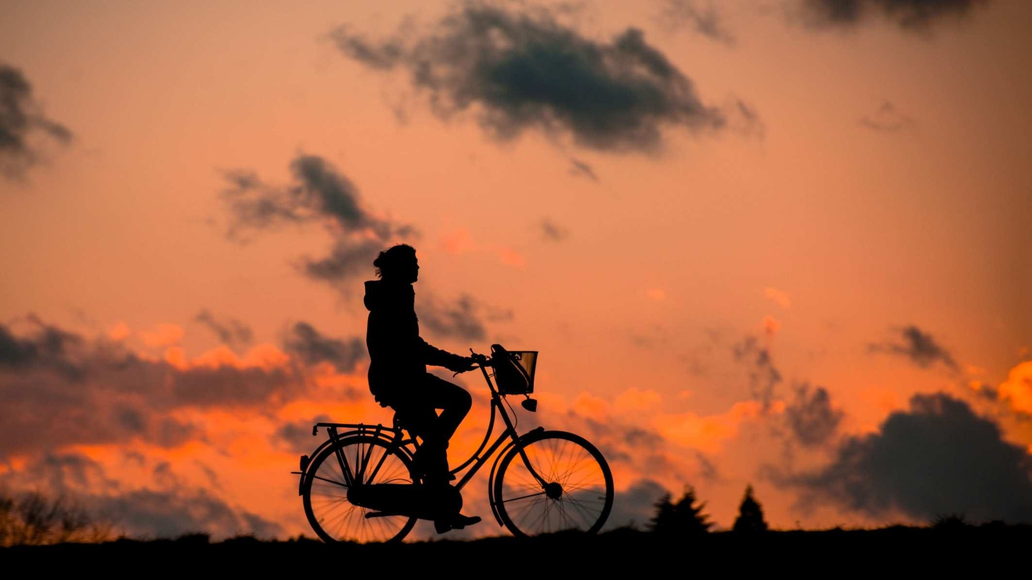 Silhouette of Person Riding a Bike during Sunset