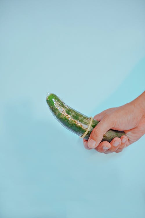 Person Holding Green Vegetable on White Background