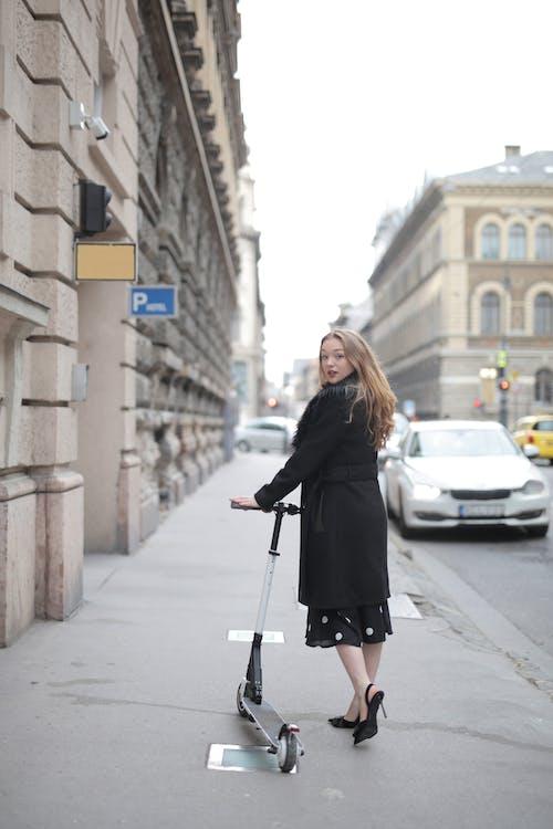 Woman in Black Long Sleeve Coat Standing on Sidewalk