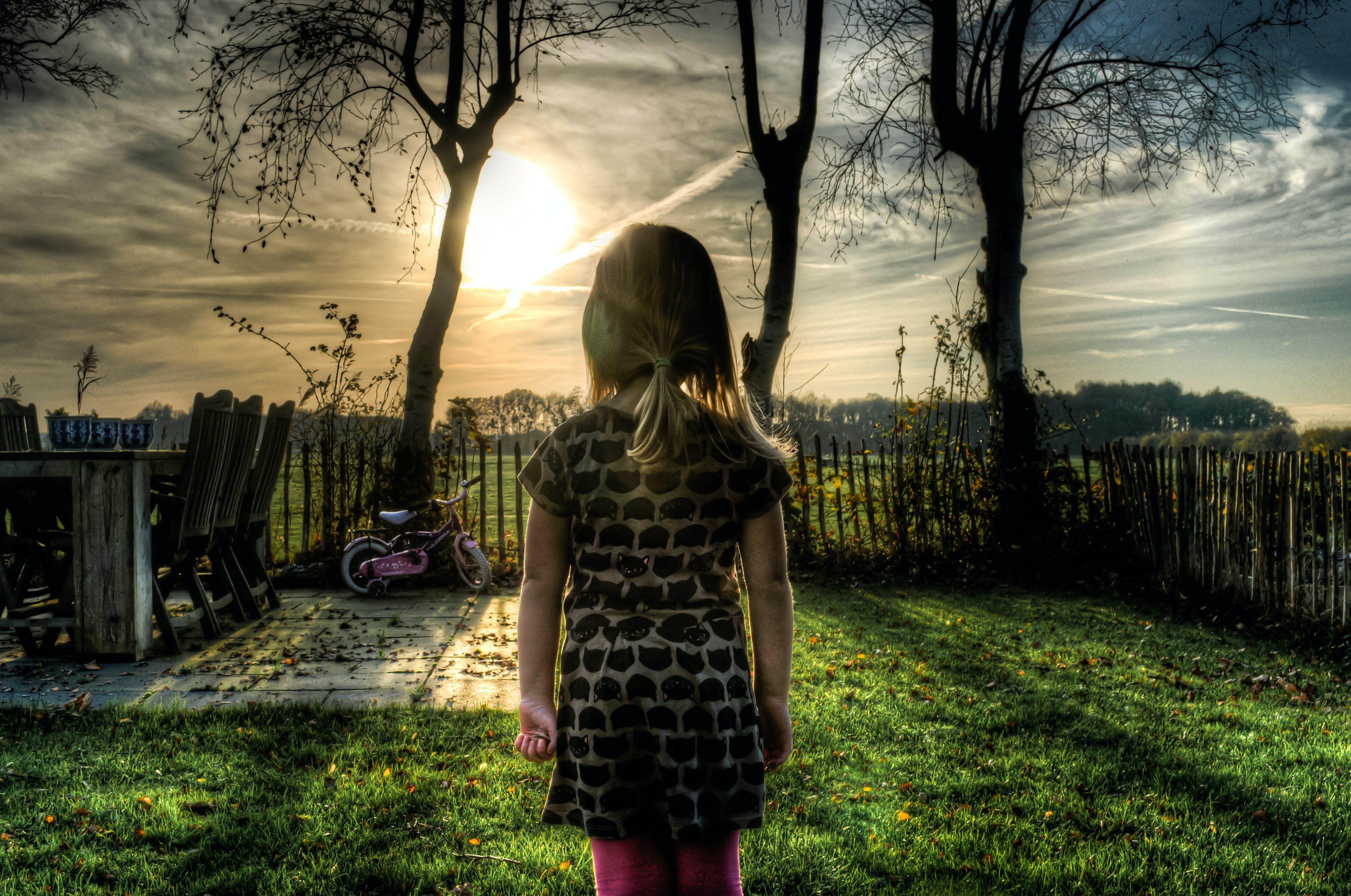Girl Facing Green Grass Field