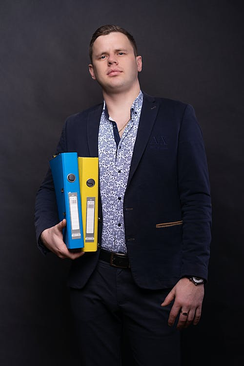 Man in Black Suit Holding Blue and Yellow Folders