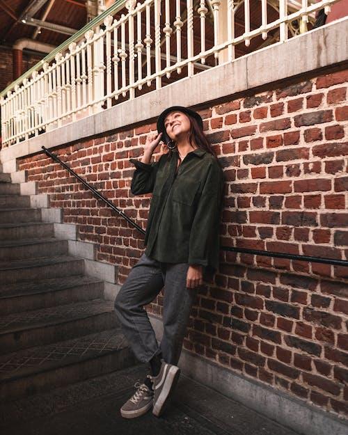 Mulher De Manga Comprida Verde Encostada Na Parede De Tijolos Ao Lado De Escadas De Concreto