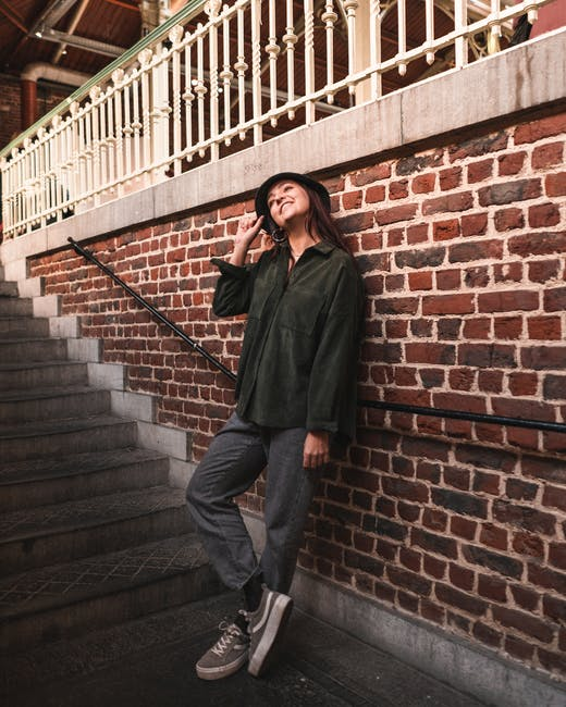 Woman in green long sleeve leaning on brick wall beside concrete stairs