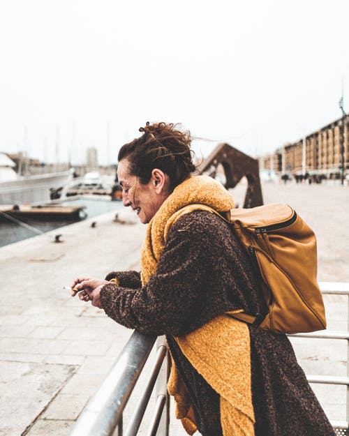 Woman in Brown Coat Leaning on Metal Hand Rail