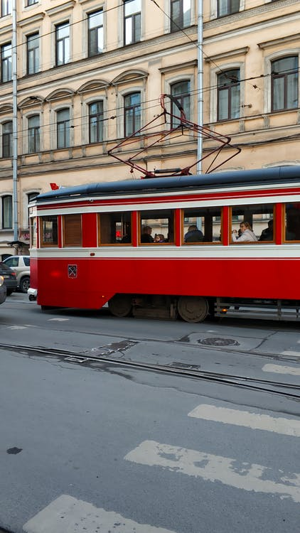 Red and White Tram on Road Near Building