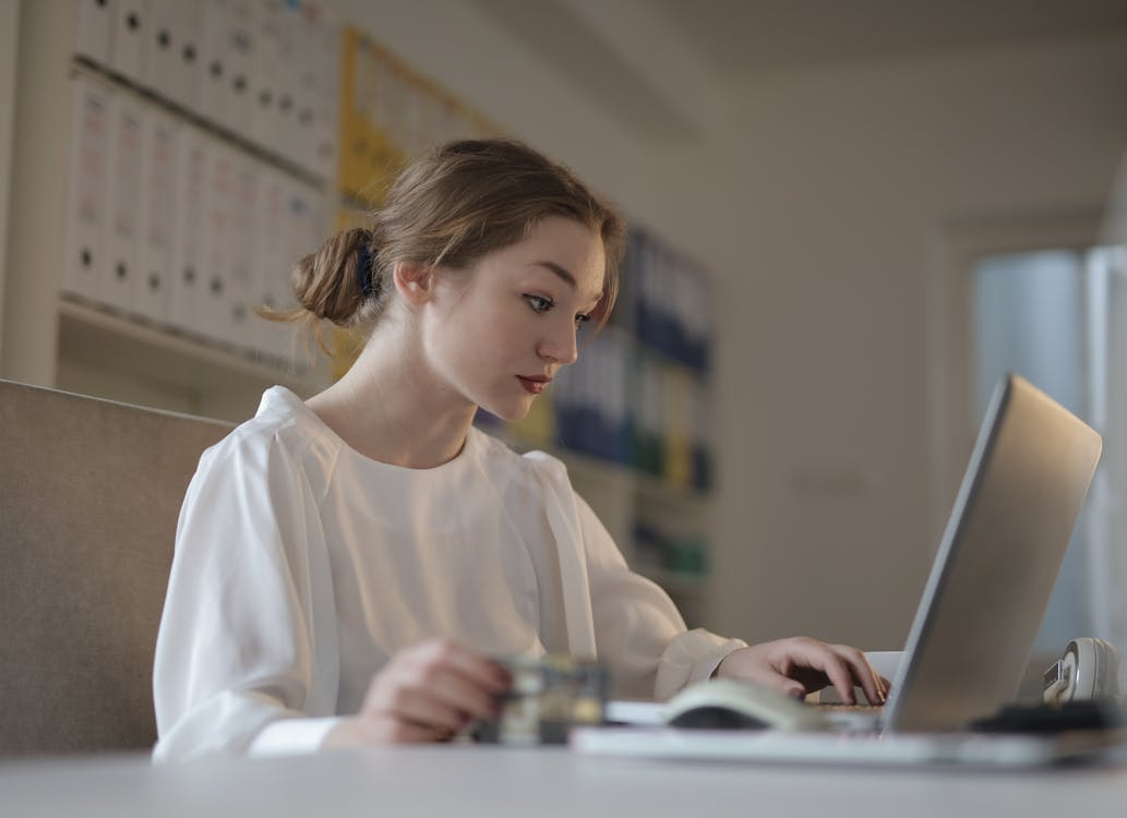 Woman In White Long Sleeve Shirt Using A Laptop