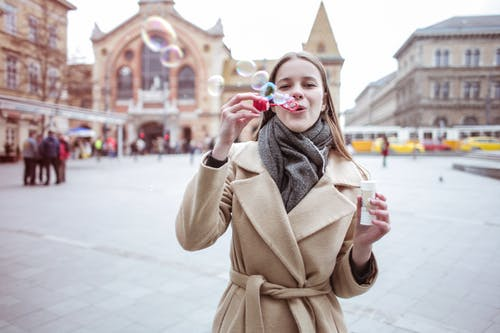 Woman in Brown Coat Blowing Bubbles