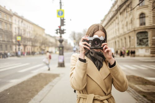 Person In Brown Coat Holding An Old Camera
