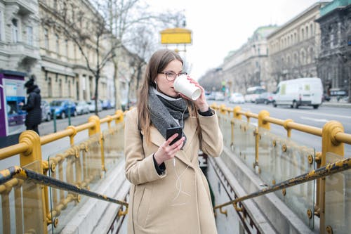 Woman In Beige Coat Holding White Coffee Cup