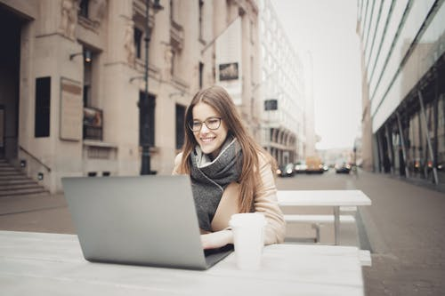 Woman In Brown Coat Using A Laptop