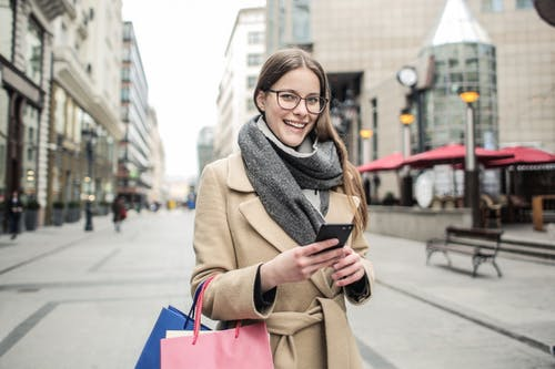 Woman In Brown Coat Holding Smartphone