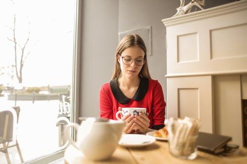 Woman In Red Long Sleeve Holding White Ceramic Mug