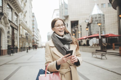 Woman in Brown Coat and Gray Scarf Holding Shopping Bags