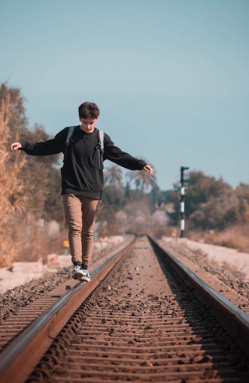 Man in Black Sweater Walking on Train Rail