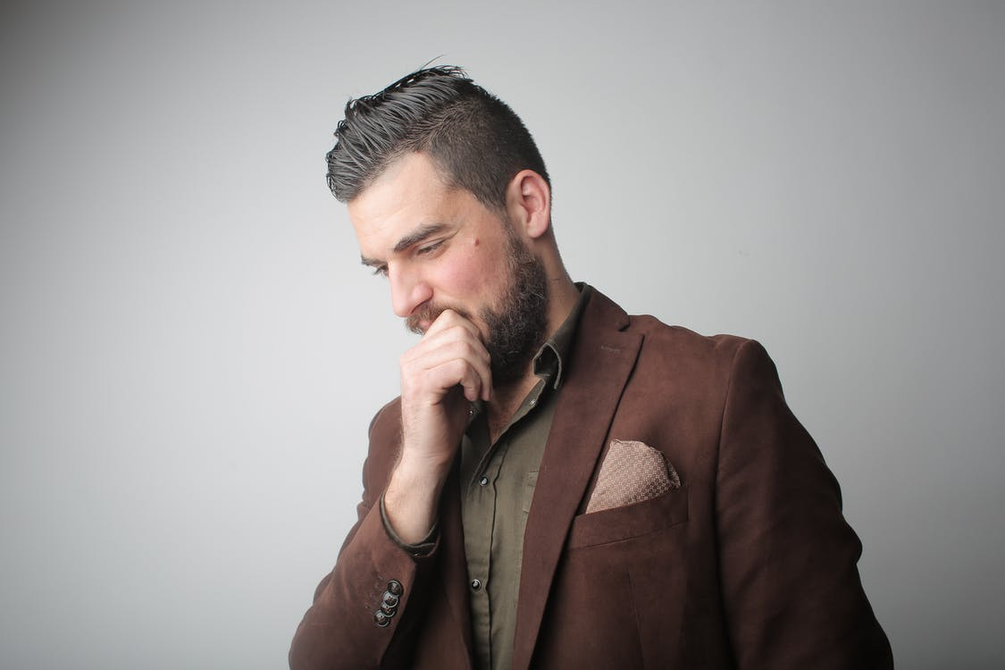 Pensive Man in Brown Coat Holding His Chin