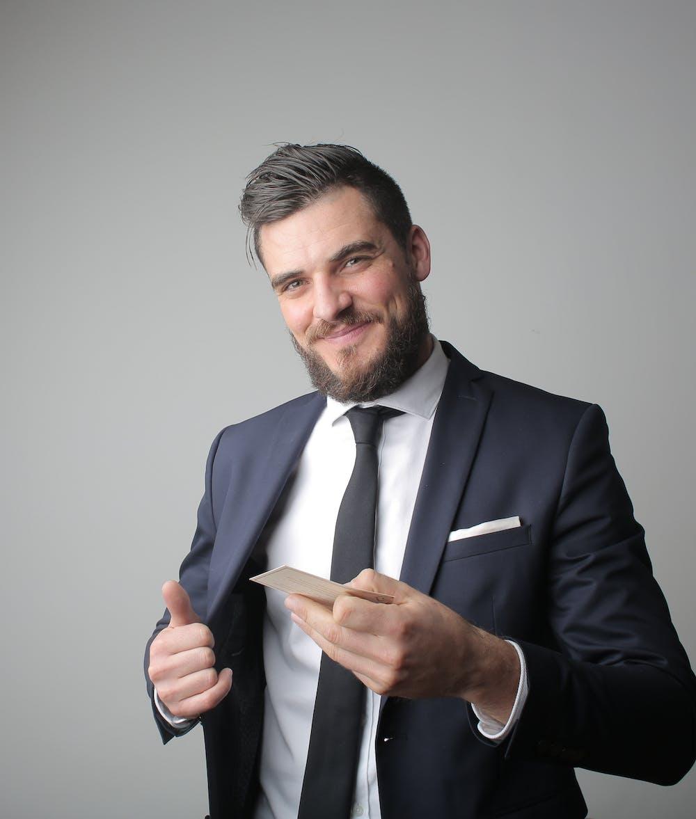 Man in formal suit jacket smiling. | Photo: Pexels